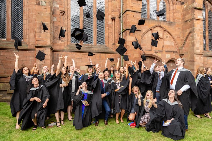 Graduation July 2019, graduation July 2019, group of students in front of Carlise cathedral throwing their graduation hats into the air