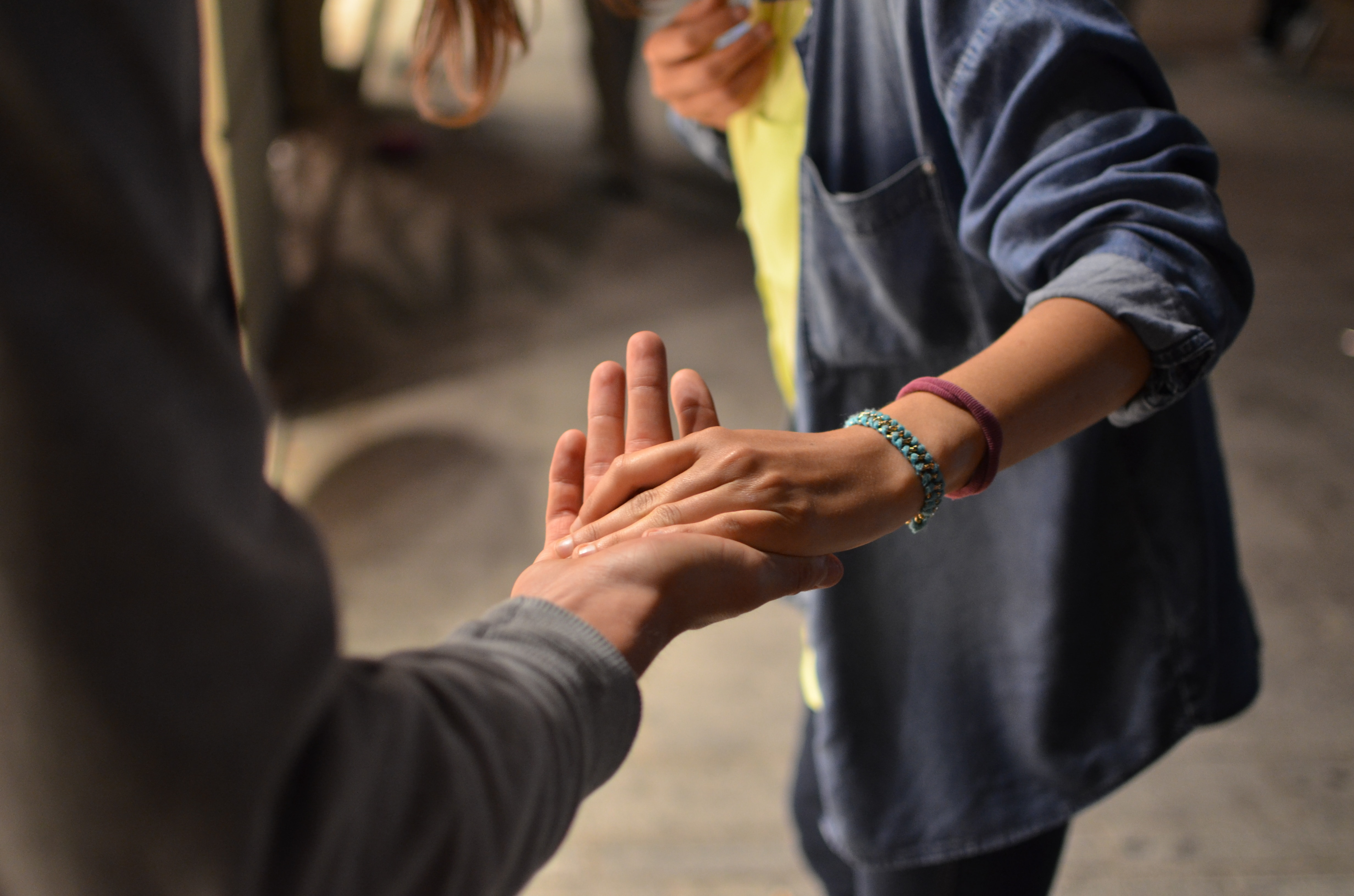 Two people holding hands to show support