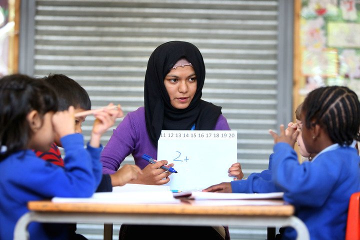 female primary school teacher, sat down with 4 young children, holding a small whiteboard