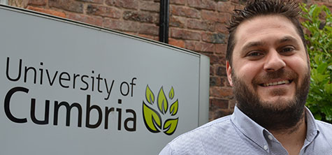 A photo of Theo stood by the sign for University of Cumbria