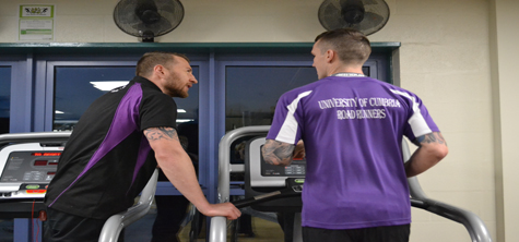 Two men in sports gear, one on treadmill