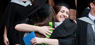 Students hugging at graduation ceremony
