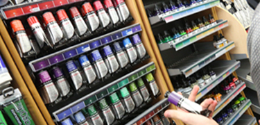 A person looking at a selection of paints