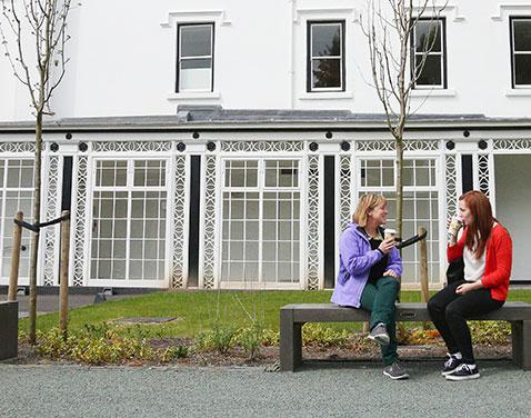 two students sitting outside Scale Howe. Original file name: Ambleside-1.jpg