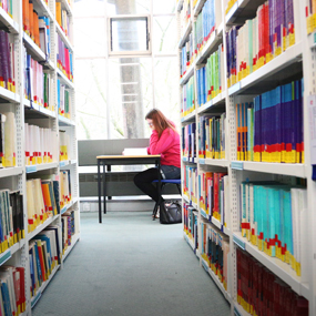 A corridor of library shelves with a woman sat at a table at the end