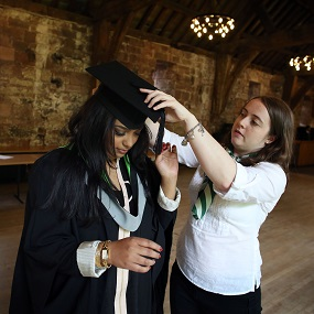 A person helping a student with her graduation clothes