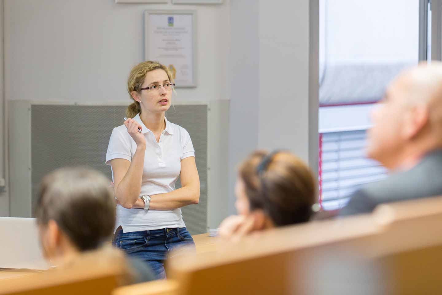 woman in white t-shirt and glasses teaching class