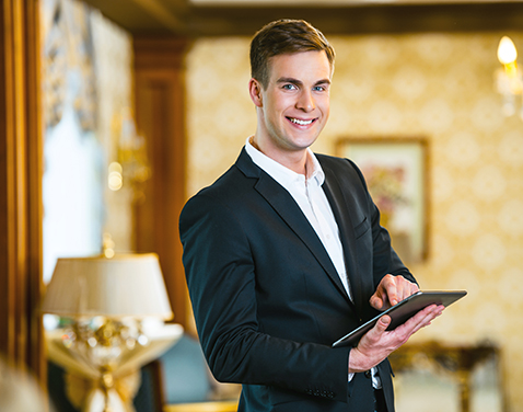 Young man with a tablet in a posh drawing room